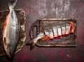Cutting fresh salmon on a cutting Board. On rustic background. - PhotoDune Item for Sale