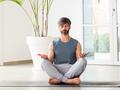 Barefoot man meditating in the Padmasana or Lotus pose - PhotoDune Item for Sale
