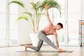 Young man doing a Parivrtta trikonosana or triangle yoga pose - PhotoDune Item for Sale