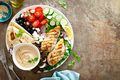 Chicken breast grilled with fresh vegetables, olives, feta cheese, flatbread and hummus, top view - PhotoDune Item for Sale