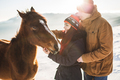 Couple petting and feeding horse with pleasure in shiny sunlight. Winter in mountains - PhotoDune Item for Sale