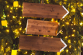 Three wooden pointer on background with fir branches in garlands. Christmas lights - PhotoDune Item for Sale