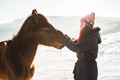 Happy girl gently stroking horse in shiny sunlight. Winter in mountains - PhotoDune Item for Sale