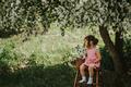 Asian girl sitting on stepladder under an apple tree - PhotoDune Item for Sale