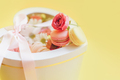 Macarons with different types of flowers in a box in the shape of a heart against a yellow - PhotoDune Item for Sale