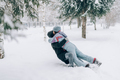 A guy and a girl are playing in the snow. Falling hugging people into the snow - PhotoDune Item for Sale