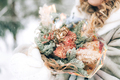 Woman holding a beautiful bouquet of flowers in her hands on a background of snow. Winter time. Gift - PhotoDune Item for Sale