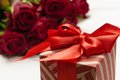 A bouquet of red roses, gift and hearts on table. Concept Women's Day or St. Valentine. Copy - PhotoDune Item for Sale