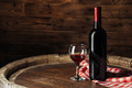 Bottle and glass of red wine on wooden barrel shot with dark wooden background - PhotoDune Item for Sale