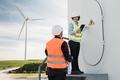 Engineer people work at alternative energy farm station with turbine on background - PhotoDune Item for Sale
