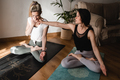 Young people doing pranayama exercises during studio yoga class indoor at home - Focus on left woman - PhotoDune Item for Sale