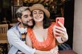 Happy couple having fun doing selfie outdoor in bar restaurant - Tourist, summer travel concept - PhotoDune Item for Sale