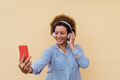 African senior woman listening music on mobile phone app while wearing headphones outdoor - PhotoDune Item for Sale