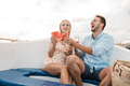 Happy young couple cheering with champagne and eating fruits on sail boat in summer vacation - PhotoDune Item for Sale