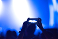 Hand holding smart phone at live music festival. Concert stage lights on viewfinder - PhotoDune Item for Sale