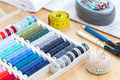 Various sewing accessories, spools and thread, schemes and cloth on wooden table, horizontal - PhotoDune Item for Sale