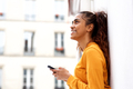 Close up side portrait of happy young woman leaning against white wall holding cellphone - PhotoDune Item for Sale
