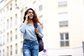 happy young woman walking and talking with cellphone and bag in city - PhotoDune Item for Sale