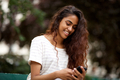 Close up beautiful young indian woman smiling in park and looking at mobile phone - PhotoDune Item for Sale