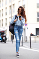 Full length young woman walking with mobile phone and bag in city - PhotoDune Item for Sale