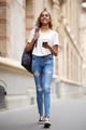 Full length female university student walking on campus with mobile phone and bag - PhotoDune Item for Sale