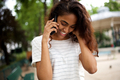Close up happy young indian woman talking with phone in park - PhotoDune Item for Sale