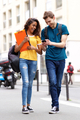 Full length two happy university students walking in city looking at mobile phone - PhotoDune Item for Sale