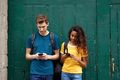 male and female university students standing by green wall looking at mobile phone - PhotoDune Item for Sale