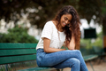young indian woman sitting on park bench talking with mobile phone - PhotoDune Item for Sale