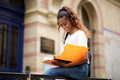 female college student reading notes outside on campus - PhotoDune Item for Sale