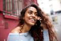 Close up smiling young woman talking with mobile phone in city - PhotoDune Item for Sale