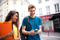 two college students walking in city looking at mobile phone - PhotoDune Item for Sale