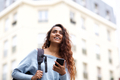 happy young Indian woman walking with cellphone and bag in city - PhotoDune Item for Sale