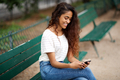 Side of young indian woman sitting on park bench looking at phone - PhotoDune Item for Sale