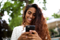 Close up smiling young indian woman looking at mobile phone in park - PhotoDune Item for Sale