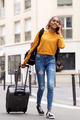 Full body happy young indian woman walking talking in city with suitcase - PhotoDune Item for Sale