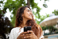 Close up smiling young indian woman holding cellphone in park and looking away - PhotoDune Item for Sale