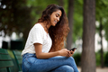 Side of young indian woman sitting on park bench looking at mobile phone - PhotoDune Item for Sale