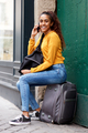 young travel woman sitting in city talking with mobile phone - PhotoDune Item for Sale