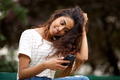 Close up beautiful young indian woman smiling in park and looking at phone - PhotoDune Item for Sale