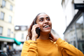 Close up smiling young indian woman talking with mobile phone in city and looking up - PhotoDune Item for Sale