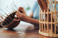 Woman weaves basket of paper tubes on wooden table - PhotoDune Item for Sale
