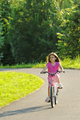Young girl riding her bicycle down a curving rural road - PhotoDune Item for Sale