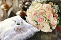 Two gold wedding rings displayed on cushion with bridal bouquet - PhotoDune Item for Sale