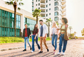Group of friends walking in a line down an urban street - PhotoDune Item for Sale