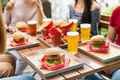 Serving of hamburgers and cold beers at a restaurant table - PhotoDune Item for Sale