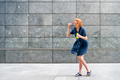 Carefree redhead woman celebrating blowing soap bubbles in town - PhotoDune Item for Sale