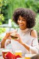 Vivacious happy young black woman eating a hamburger - PhotoDune Item for Sale