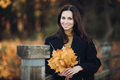Picture of attractive woman goes for a walk in autumn park and holds a bouqet of yellow leaves - PhotoDune Item for Sale