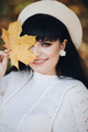 Portrait of attractive woman walks to the autumn park and enjoys of her life with yellow leave - PhotoDune Item for Sale